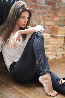 Привлекательная молодая женщина позирует в белой рубашке и джинсах