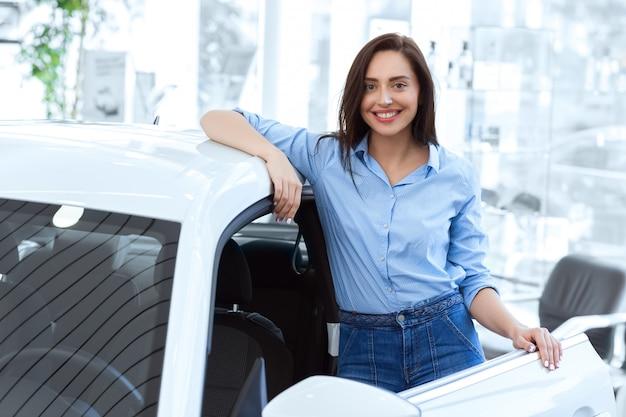 魅力的な若い女性が自動車販売店で新しく買った車に近いポーズ
