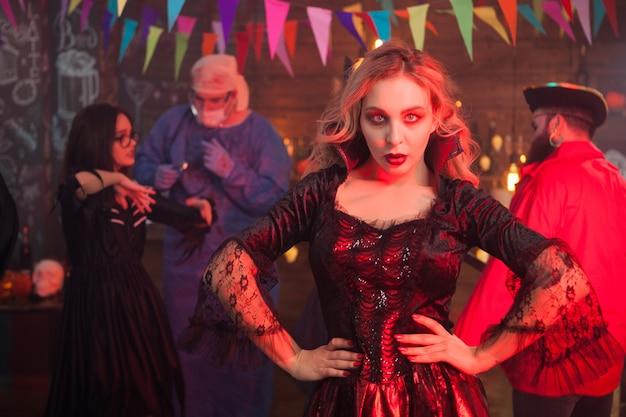 ハロウィーンのお祝いで魔女の衣装でカメラにポーズをとる魅力的な若い女性。男はバックグラウンドで海賊のような格好をした。