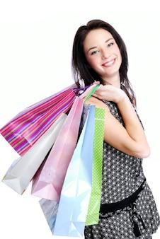 Привлекательная молодая женщина позирует с сумками