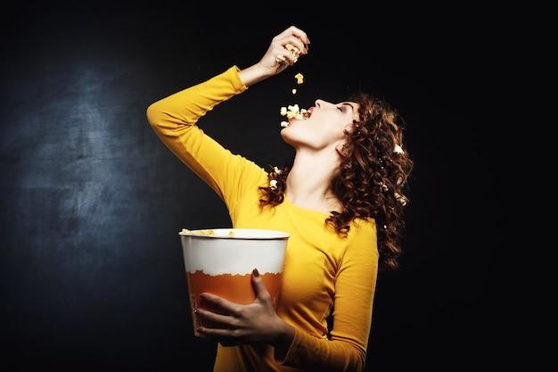 Popcorn di versamento della giovane donna attraente in bocca che tiene grande secchio