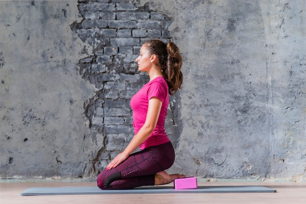 An attractive young woman practicing yoga against weathered wall