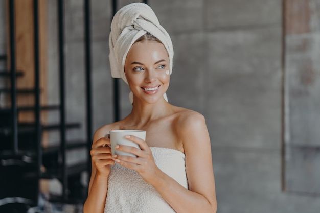 Attractive young woman puts moisturizing cream on face after showering, smiles broadly, wrapped in towels, drinks coffee, poses indoor, thinks about something pleasant. beauty skin care concept