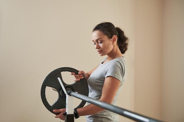 Привлекательная молодая женщина кладет металлический диск на штангу перед тренировкой со штангой. подходящая женщина, бодибилдинг.