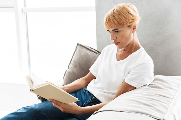 Attractive young woman reading book while sitting on a couch at home