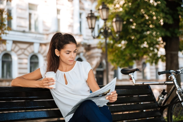Привлекательная молодая женщина читает газету, сидя на скамейке с чашкой кофе