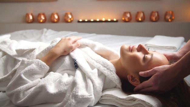 Привлекательная молодая женщина получает массаж головы в спа-центре.