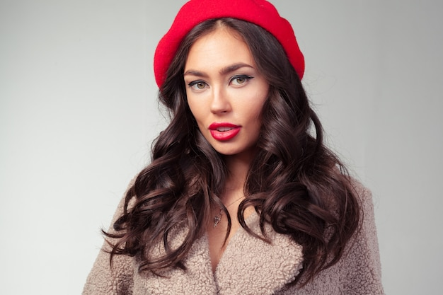 Attractive young woman in red beret and fashionable coat