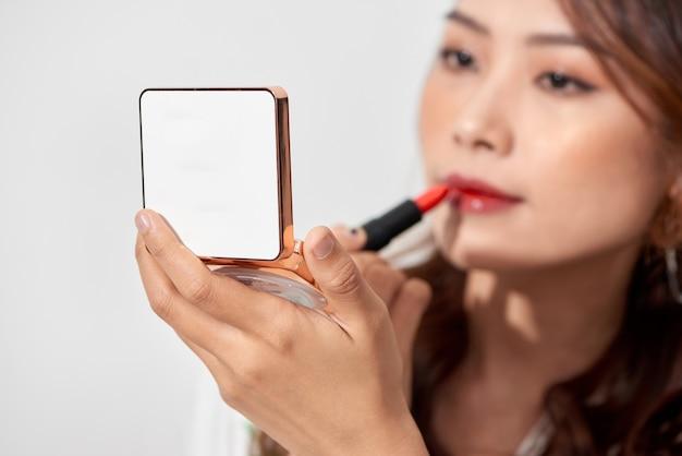 晴れた日にハンドヘルドミラーパウダーボックスを持って化粧口紅をリフレッシュする魅力的な若い女性