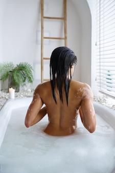 魅力的な若い女性は、泡風呂、背面図でリラックスします。バスタブの女性、スパの美容とヘルスケア、バスルームのウェルネストリートメント、背景の小石とキャンドル
