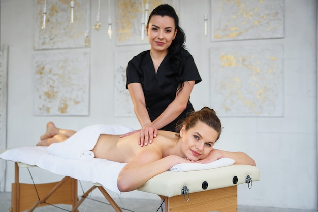 Attractive young woman relaxing during procedure in massage centre.