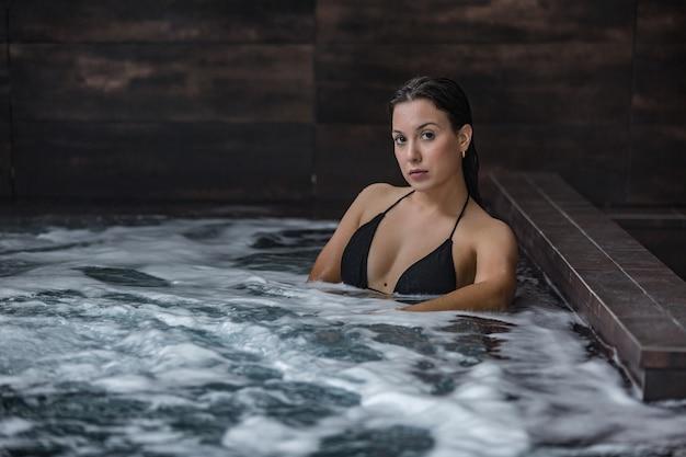 Привлекательная молодая женщина, расслабляющаяся в спа-бассейне
