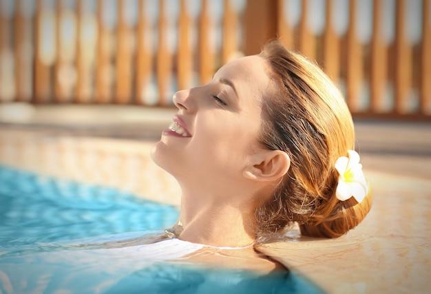 수영장에서 편안한 매력적인 젊은 여자