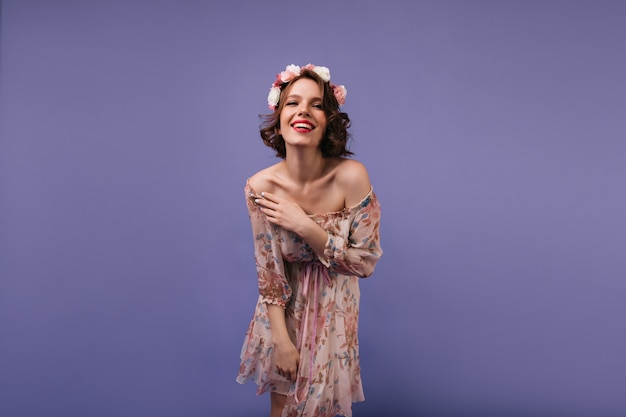 Attractive young woman in romantic attire expressing happiness. debonair female model with flowers on her head smiling.