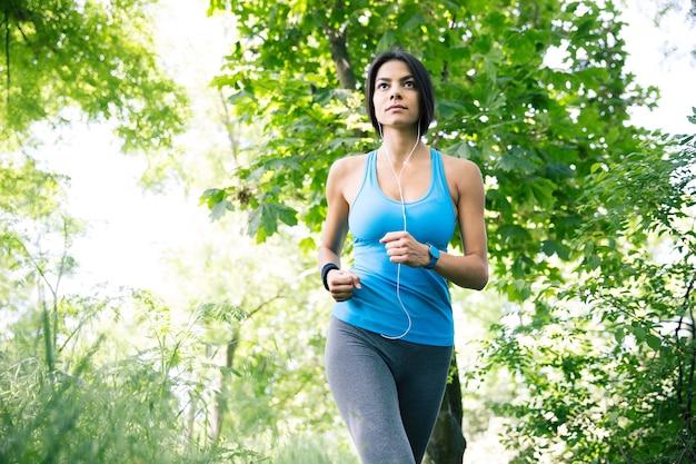公園で走っている魅力的な若い女性