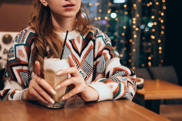 一杯のコーヒーとカフェのテーブルに座っている魅力的な若い女性