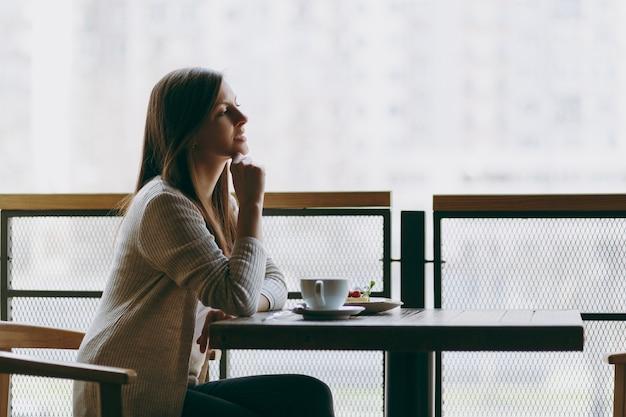 魅力的な若い女性は、カプチーノ、ケーキ、自由時間のレストランでリラックスしてテーブルのコーヒーショップの大きな窓の近くに一人で座っています。カフェで休んでいる若い女性。ライフスタイルのコンセプト。