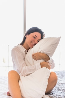 An attractive young woman sitting on bed hugging her white pillow