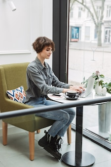 Attractive young woman sitting at the cafe table indoors, working on laptop computer, analyzing documents