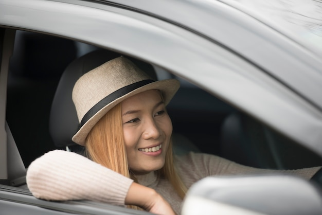 Attractive young woman sitting in the car open the window enjoy nature.