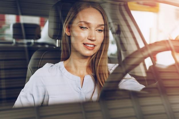 Привлекательная молодая женщина, сидящая в новой машине в автосалоне крупным планом