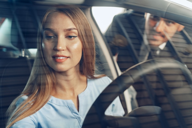 Attractive young woman sitting in new car in showroom