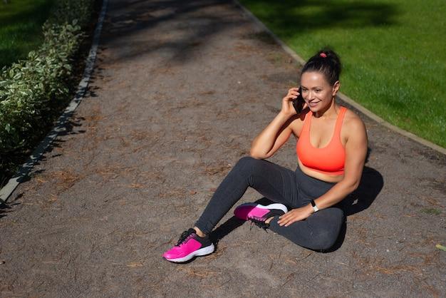 Привлекательная молодая женщина сидит на беговой дорожке в городском парке и разговаривает по мобильному телефону