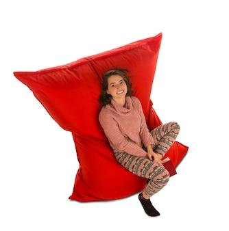 リビングルームや他の部屋の赤いお手玉のソファの椅子に座って、白で隔離の本を保持している魅力的な若い女性
