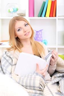 소파에 앉아 책을 읽는 매력적인 젊은 여성