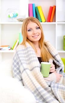 매력적인 젊은 여자, 소파에 앉아, 뜨거운 음료와 함께 컵을 들고