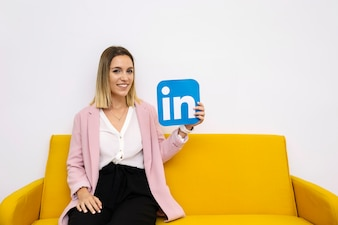 Attractive young woman sitting on sofa holding linkedin icon