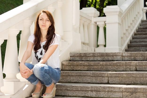 Привлекательная молодая женщина, сидящая на ступеньках