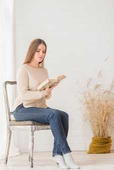 An attractive young woman sitting on wooden chair reading book