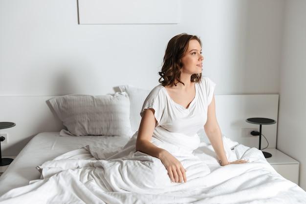 아침에 집에서 침대에 앉아 매력적인 젊은 여자