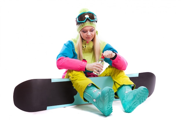 Attractive young woman in ski suit and ski glasses sit on snowboard, hold water