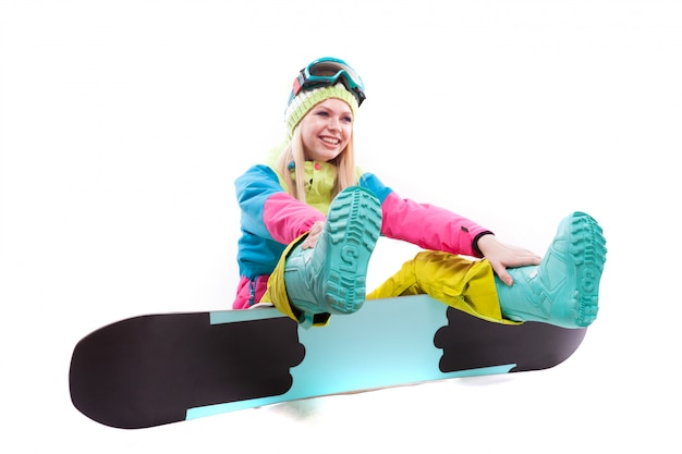 Attractive young woman in ski suit and ski glasses sit on snowboard