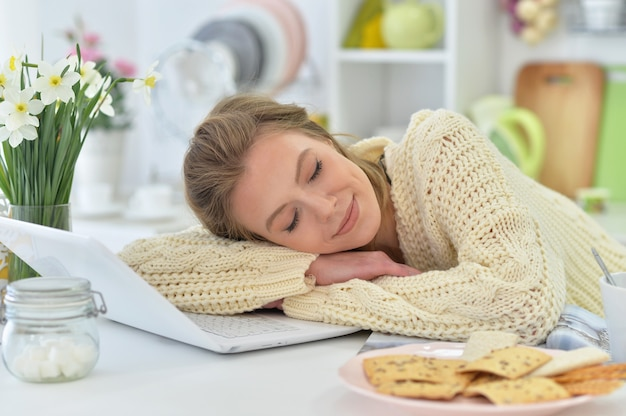 Attractive young woman sleeping on  laptop at kitchen