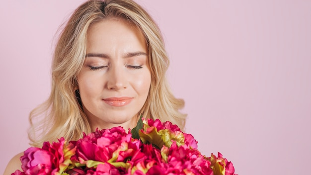 Attractive young woman smelling the flower bouquet against pink backdrop