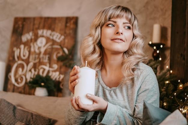 크리스마스를 축 하하는 촛불을 들고 웃 고 매력적인 젊은 여자. 새해-아늑한 인테리어