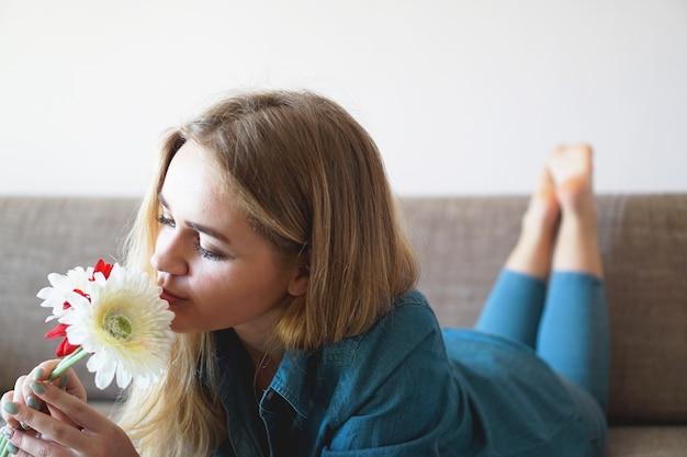Привлекательная молодая женщина нюхает букет цветов, лежащих на диване