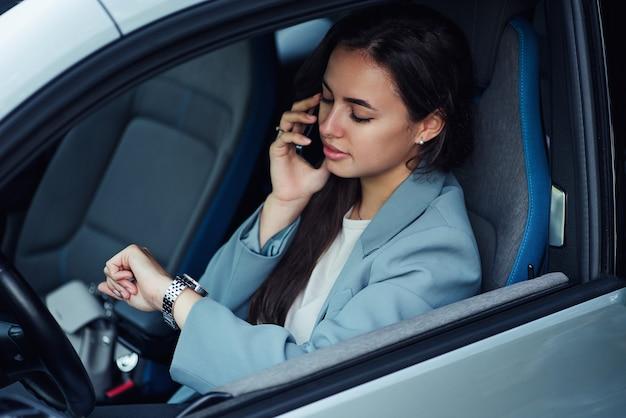 若いビジネスの車の肖像画に座っている間、魅力的な若い女性が携帯電話で話します