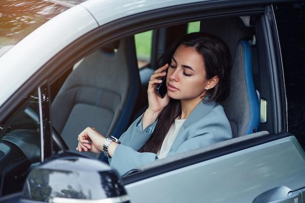 매력적인 젊은 여성은 젊은 비즈니스의 자동차 초상화에 앉아있는 동안 휴대 전화로 말합니다