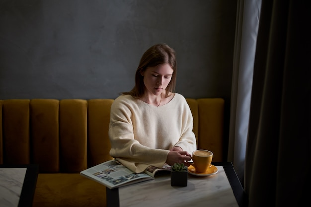 魅力的な若い女性は自由な時間をカフェに座って、入れたてのコーヒーを楽しんだり、女性の雑誌を読んだりしています。