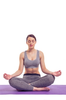 Attractive young woman in sports wear is meditating.