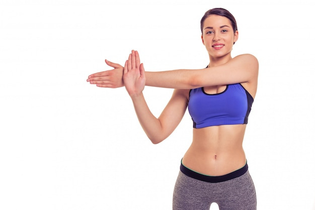 Attractive young woman in sports wear is stretching. copyspace