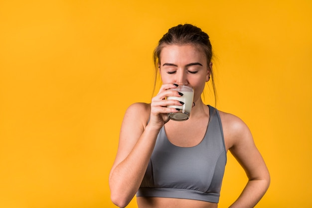 Attractive young woman in sportswear drinking milk