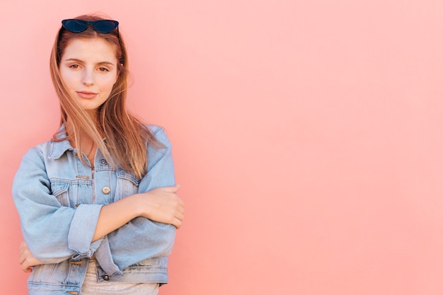 An attractive young woman standing against peach background