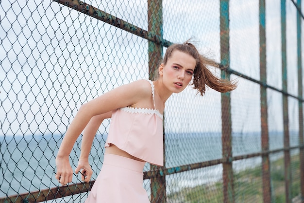 金網フェンスの近くに立ってポーズをとって魅力的な若い女性