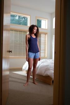 Attractive young woman standing in bedroom