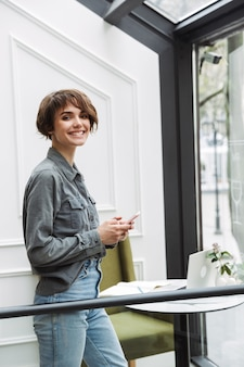 Attractive young woman standing at the cafe indoors, using mobile phone